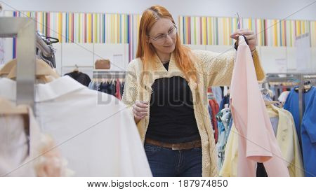 The red-haired woman wearing glasses and a knitted jacket examines pink dress in women's clothing store