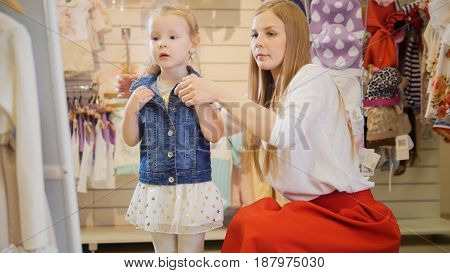 Shopping for kids - the young mother corrects daughter denim jacket in front of the mirror