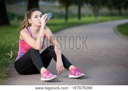 Thirsty woman drinking water to recuperate after jogging.