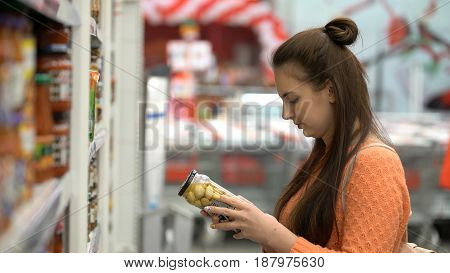 Woman buys pickled mushrooms in store or supermarket