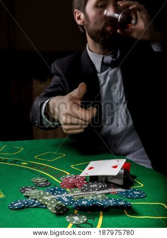 Poker player showing a losing combination in a poker cards, man drinks whiskey from grief.