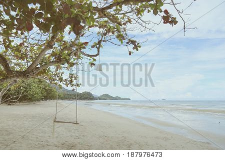 Empty wooden swing hanging on branches in sunny day near the beach of koh Chang gulf of Thailand vintage filter warm tone.