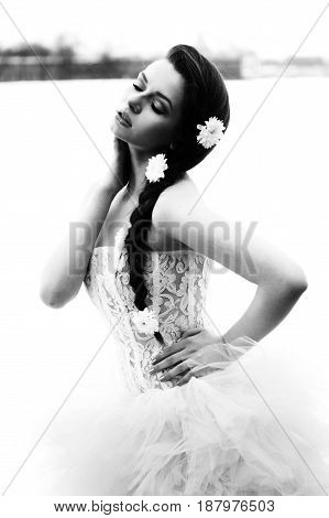 outdoors portrait of young beautiful female model in white wedding dress with flowers in her hair