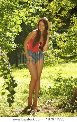 full lenght portrait of young beautiful sexy woman posing in green leaves at summer