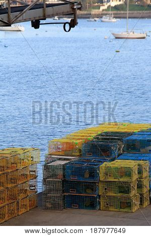 Vertical image of pier at edge of ocean, with several lobster  traps stacked and ready for fishermen to take them out for a profitable day on the water.