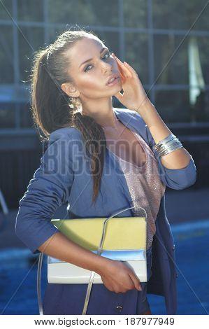 young beautiful elegant lady wearing blue coat posing outdoors