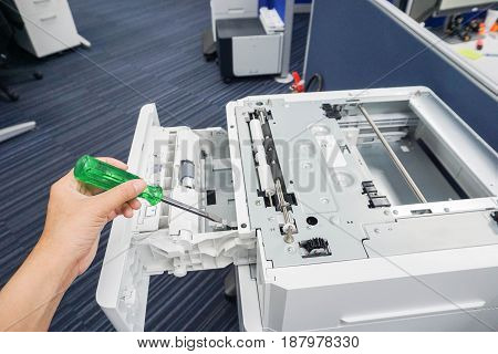 engineer left hand use green screwdriver repair office printer tray and other parts