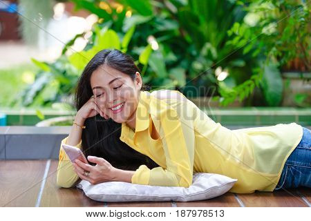 Cheerful asian woman using smart phone while lying on floor for entertainment. Happy female smiling and looking at telephone. Outdoors at the daytime with bright sunlight.