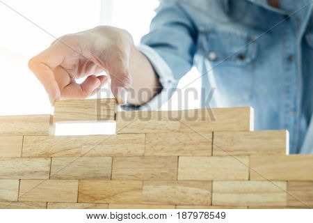 Hand Of Engineer Playing A Blocks Wood Tower Game (jenga) On Blueprint Or Architectural Project Conc