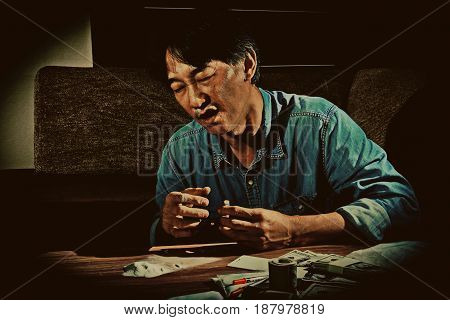 Closeup of the man is drug addict using drugs or Cocaine alone with dark vintage style substance addiction and abuse concept.