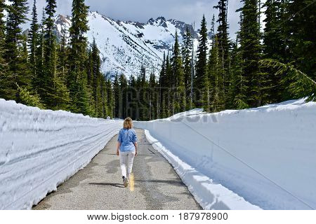 Woman walking on the road with snow walls. North Cascades National Park. Bellingham. Seattle. Cascade mountains. Washington. The United States.