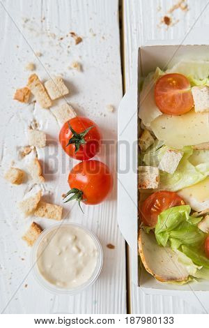 Close up top view Caesar salad in box with cherry tomatoes, croutons and white sauce