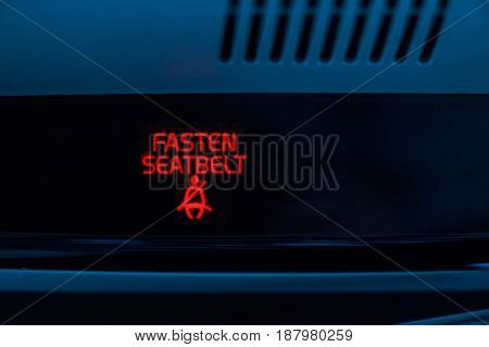 Close up red indicator in car saying fasten seatbelts