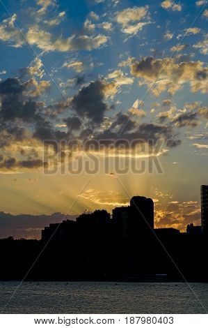 Beautiful skyscape of city with sillhouettes of buidings on river bank