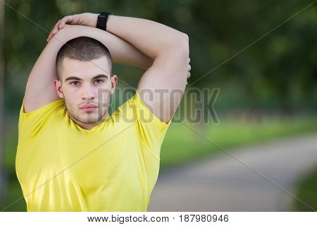 Fitness man stretching arm shoulder before outdoor workout. Sporty male athlete in an urban park warming up