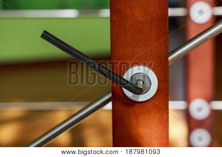 Close up metal hexagon key in hole in furniture