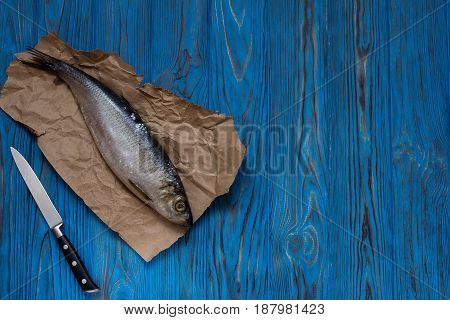 Herring on paper and knife on wooden table. Top view