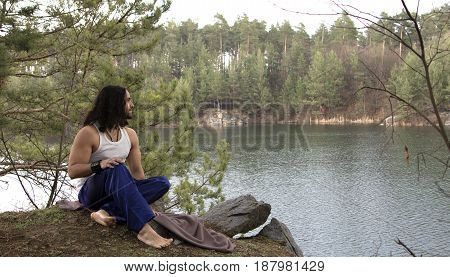 Young guy sits on high bank above the lake. Relax in nature.