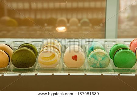 Colorful French cookies macarons lie in row on counter of store