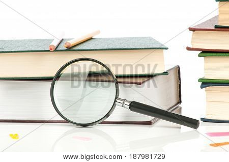 Heap of books and magnifying glass on white background