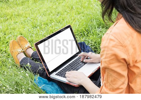 young woman sit on green grass enjoy the music with laptop Outdoors Freedom and Relax concept soft focus vintage tone