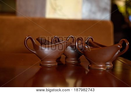 Close up empty brown gravy boats standing on table