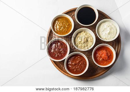 Top view of seven small bowls with different dips on wooden tray