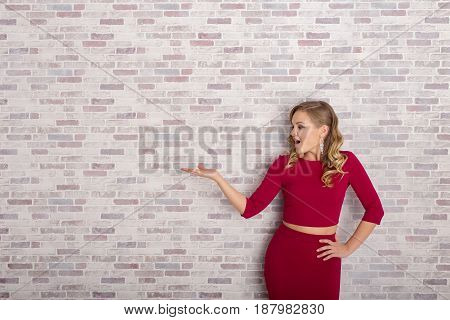 Portrait Of A Beautiful Woman In A Dress, With Her Hand Outstretched, As Though She Is Presenting So