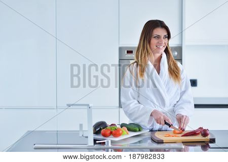 Smiling beautiful woman preparing salad at morning breakfast. Photo of young woman in bathrobe. Diet. Healthy lifestyle. poster