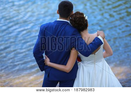 Happy Bride And Groom Embrace On Sea Background