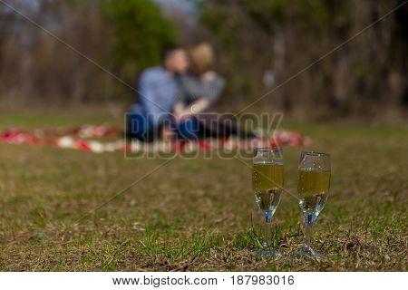 Two Champagne Glasses, Blur Couple In Background.