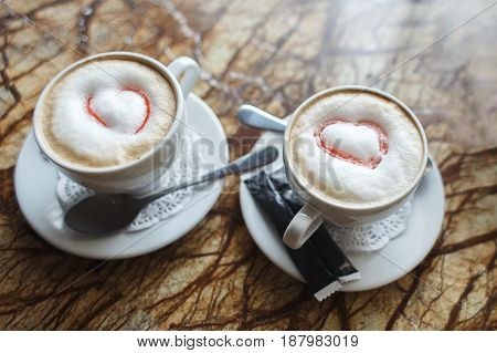 Two cups of gourmet coffee house cappuccino against on table.
