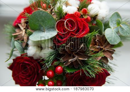 Winter Wedding Bouquet Of Red Roses With Wedding Rings.