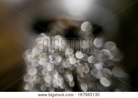 Abstract silver bokeh with blur and flare. Elegant jewelry with bokeh defocused lights.
