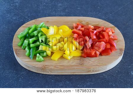 Green, red and yellow sweet paprika cut in cubes on a wooden cutting board on a dark abstract background. Step by step cooking