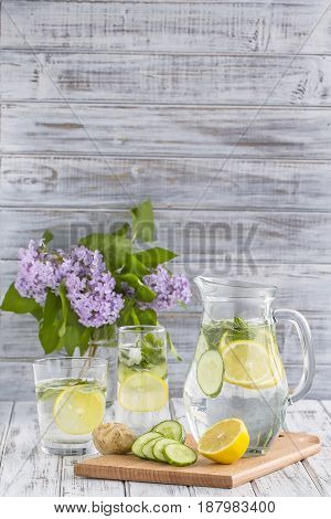 Dietary detox drink with lemon juice ginger cucumber and mint leaves in clear water with ice.