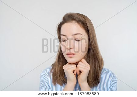 Studio portrait of young pensive girl looking down sideways thinking about something