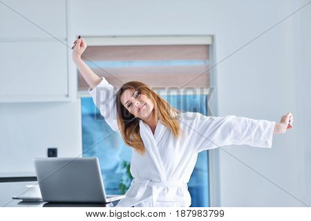 woman wearing a white bathrobe with laptop.