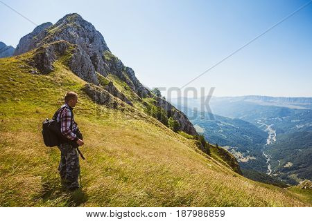 Hiker standing at viewpoint in mountain and looking at valley.