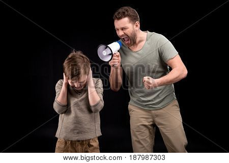 Angry Father With Megaphone Screaming At Scared Little Boy Closing Ears, Family Problems Concept