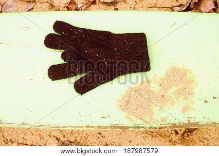 Lost Woolen Gloves On Green Bench. Sandy Gren Wooden Bench.  Sandbox With Dirty Sand In Kindergarden