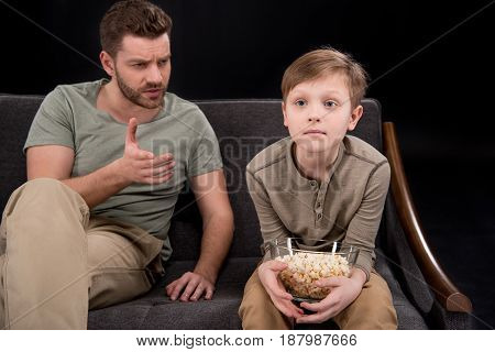 Father Talking And Gesturing To Little Son Sitting On Sofa With Popcorn In Bowl, Family Problems Con