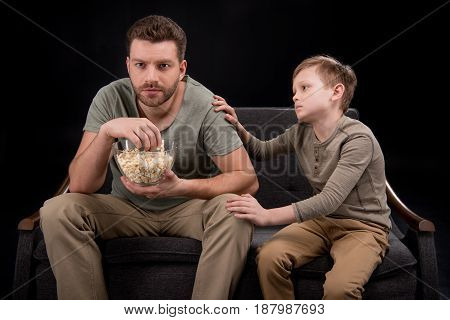 Little Boy Trying To Talk With Father Eating Popcorn And Watching Tv On Sofa, Family Problems Concep