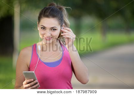 Young lady jogging on a park road having break and listening to music