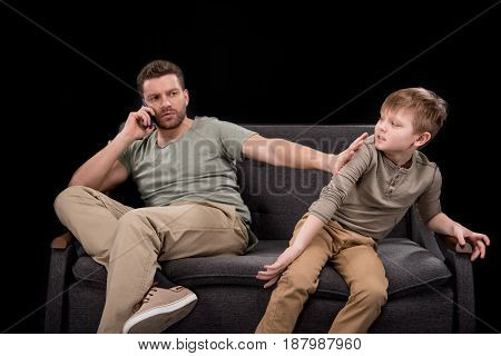 Bearded Man Talking On Smartphone And Pushing Little Son Sitting On Sofa, Family Problems Concept