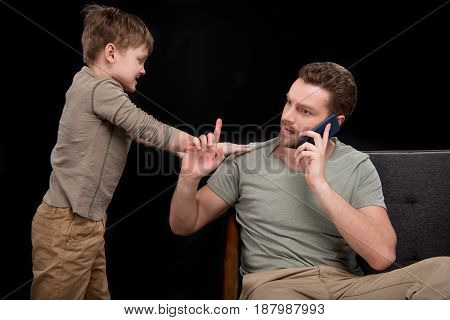 Upset Little Boy Trying To Talk With Father Talking On Smartphone, Family Problems Concept