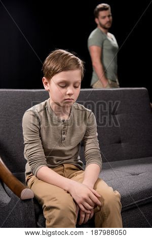 Upset Little Boy Sitting On Sofa And Father Standing Behind, Family Problems Concept
