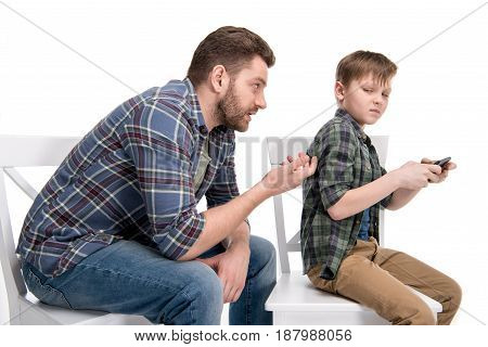 Father Talking With Little Son Sitting On Chair And Using Smartphone, Family Problems Concept