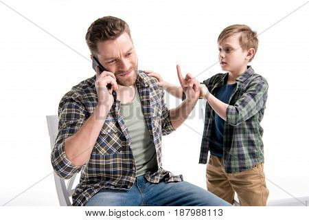 Little Boy Trying To Talk With Father Talking On Smartphone And Gesturing, Family Problems Concept