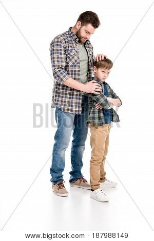 Father Embracing Serious Son Standing With Crossed Arms, Family Problems Concept